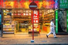 Traditional Chinese medicine store, Hong Kong. Hong Kong, China - February 16, 2014: Man passes by neon-lighted traditional Chinese medicine store on February 16 Royalty Free Stock Photography
