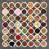 Traditional Chinese Medicine. Selection with a large collection of herbs in white porcelain bowls on marble background royalty free stock image
