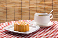 Traditional Chinese moon cakes on table setting with teacup. Stock Photo