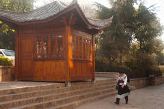 Traditional Chinese Naxi dressed woman walking through Lijiang D Royalty Free Stock Image