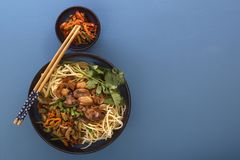 Traditional Chinese noodles noodles with fried meat and salad in a porcelain plate on a blue table. stock images
