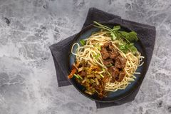 Traditional Chinese noodles noodles with fried meat and salad in a porcelain plate on a gray table. stock images