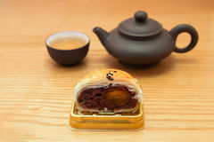 Traditional chinese snack of preserved egg cakes cut out with tea. On a wood table Royalty Free Stock Photos