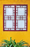 Traditional Chinese Square Window. GUILIN, CHINA - JULY 2010 - Exterior view of a traditional chinese-style wooden window set against a bright yellow painted Stock Photos