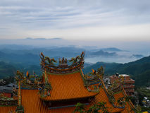 Traditional Chinese style roof in yellow with misty landscape se stock photos