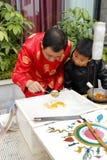 Traditional chinese sugar painting. Folk artist wear red dress and show  traditional chinese sugar painting with hot maltose, xiamen city, china Royalty Free Stock Image