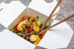 Traditional Chinese takeaway fast food - buckwheat soba noodles with vegetables and shrimps packed in a cardboard box royalty free stock photos