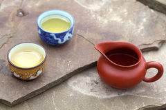 Traditional chinese tea ceremony accessories (cups and pitcher). On the stone table Stock Photography