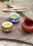 Traditional chinese tea ceremony accessories (cups and pitcher). On the stone table Stock Images