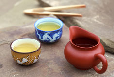 Traditional chinese tea ceremony accessories (cups and pitcher). On the stone table, selective focus on cup Stock Image