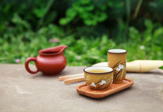 Traditional chinese tea ceremony accessories (tea cups and pitch. Er) on the stone table, selective focus on cup Royalty Free Stock Photos