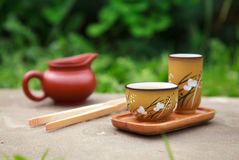 Traditional chinese tea ceremony accessories (tea cups and pitch. Er) on the stone table, selective focus on cup Stock Photography