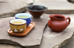 Traditional chinese tea ceremony accessories (tea cups and pitch. Er) on the stone table, selective focus on cup Royalty Free Stock Image