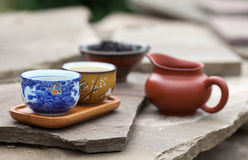 Traditional chinese tea ceremony accessories (tea cups and pitch. Er) on the stone table, selective focus on cup Royalty Free Stock Images