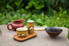 Traditional chinese tea ceremony accessories (tea cups, pitcher. And black puer tea) on the stone table, selective focus on cup Stock Photo