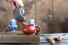 Traditional chinese tea ceremony accessories on the tea table. Traditional chinese tea ceremony accessories, Pouring tea from teapot, on the tea table Stock Photos