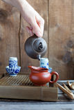 Traditional chinese tea ceremony accessories on the tea table. Traditional chinese tea ceremony accessories, Pouring tea from teapot, on the tea table Stock Photography