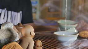 Traditional Chinese Tea Ceremony and pour the tea in a glass of the clay. Pouring Tea With The Help Of Ladle