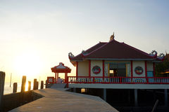 Traditional Chinese temple building next to the ocean with sunset Royalty Free Stock Photos
