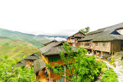 Traditional chinese wodden house in the rice fields by Longsheng Stock Photos