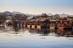 Traditional Chinese wooden recreation boats. Are moored along West Lake coast. Famous park in Hangzhou city, China royalty free stock image