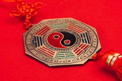 Traditional chinese yin and yang talisman on red surface. Close-up shot of traditional chinese yin and yang talisman on red surface stock images