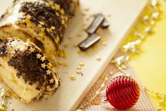 Traditional Christmas biscuit roll with chocolate cream,chocolate chips and gold stars on the holiday table close-up. royalty free stock images