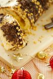 Traditional Christmas biscuit roll with chocolate cream,chocolate chips and gold stars on the holiday table close-up. stock image