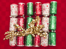 Traditional Christmas crackers on red cloth Royalty Free Stock Image