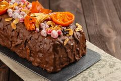 Traditional christmas fruit cake in chocolate glaze on wooden ba. Traditional christmas fruit cake in chocolate glaze decorated with cranberries, almond flakes Royalty Free Stock Photo