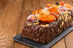 Traditional christmas fruit cake in chocolate glaze on wooden ba. Traditional christmas fruit cake in chocolate glaze decorated with cranberries, almond flakes Stock Photography