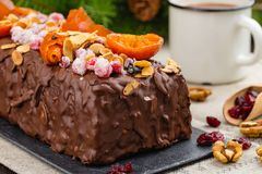 Traditional christmas fruit cake. Festive English cuisine. Traditional christmas fruit cake in chocolate glaze decorated with cranberries, almond flakes and Royalty Free Stock Image