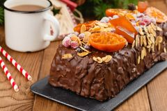 Traditional christmas fruit cake pudding in chocolate glaze. Decorated with cranberries, almond flakes and oranges on festive xmas background. British rum cake Stock Images