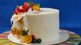 Traditional Christmas fruit cake with white frosting and sugared fruits. Cream cake with kumquat, cranberries. Strawberries stock image