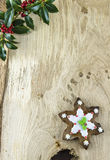 Traditional Christmas gingerbread cookie. Traditional Christmas gingerbread snowflake shaped cookie on wooden table with a branch of hollie Royalty Free Stock Images
