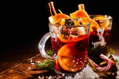 Traditional Christmas Gluhwein with cinnamon. Traditional Christmas Gluhwein or mulled sweet spicy red wine with cinnamon served in two glass mugs with candy Royalty Free Stock Images