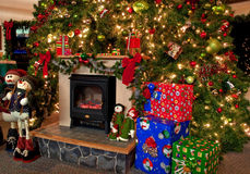 Traditional Christmas Hearth Scene. This image is a traditional Christmas hearth scene with a huge decorate Christmas tree with lights and ornaments, gifts and stock images