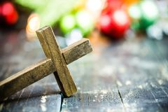 Traditional Christmas Holiday Ornaments and Christian Cross on a. Traditional Christmas holiday ornaments and a holy Christian cross on a dark stained wooden Royalty Free Stock Photo