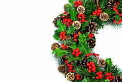 Traditional Christmas holly wreath. A traditional Christmas holly wreath comprising holly with vivid red berries, pine, cypress and cones with room for text royalty free stock images