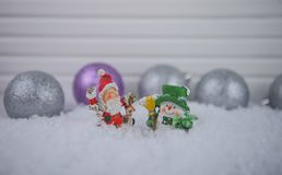 Christmas photography image of Santa Claus with snowman ornaments in snow with glitter colored tree decorations in background Stock Image
