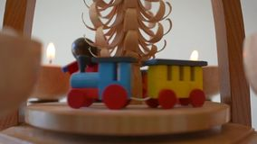 Traditional Christmas pyramid with candles showing Santa and a toy train. Traditional colourful wood crafted Christmas decoration stock footage