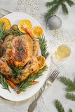 Traditional Christmas roasted chicken garnish orange, carrot, and rosemary on light table. Top view. Copy space. stock photos