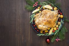 Traditional Christmas roasted chicken with potatoes and rosemary on wooden table. Top view. royalty free stock photo