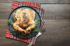 Traditional Christmas roasted chicken with spices and rosemary on wooden table. Top view. Copy space royalty free stock photos