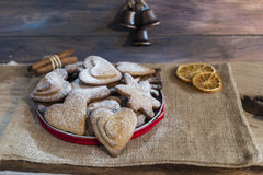 Traditional Christmas spiced cookies. Assortment of traditional Christmas spiced cookies in a tin, two slices of dried orange and sticks of cinnamon Royalty Free Stock Photo