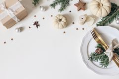 Traditional Christmas table place setting. Golden cutlery, porcelain plate, fir tree branches, gift box, pine cones and