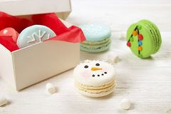 Traditional christmas themed french macaroons sweets in the form of snowman, snowflake, christmas tree and santa`s belly with can Royalty Free Stock Images