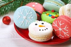 Traditional christmas themed french macaroons sweets in the form of snowman, snowflake, christmas tree and santa`s belly with can Stock Images