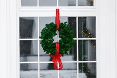Traditional Christmas wreath hanging on entrance door. Festive mood. Holiday concept stock images