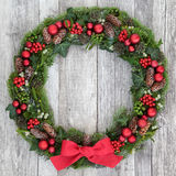Traditional Christmas Wreath. With red bow, bauble decorations, holly, mistletoe, ivy, snow covered winter greenery on distressed white wood background stock photos